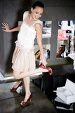 Woman trying on high-heeled shoes in a shoe shop stock images