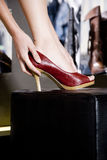 Woman trying on high-heeled shoes in a shoe shop, close-up of foot royalty free stock images