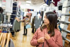 Woman trying jacket in mall. Asian young woman portrait Stock Photography