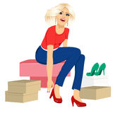 Woman trying many fashionable shoes. Attractive blonde woman trying many fashionable shoes Royalty Free Stock Photo