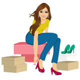 Woman trying many fashionable shoes. Attractive brunette woman trying many fashionable shoes Royalty Free Stock Image
