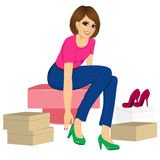 Woman trying many fashionable shoes. Attractive brunette woman trying many fashionable shoes Royalty Free Stock Photography