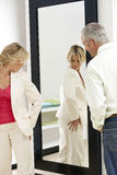 Woman trying on new clothes in fitting room, looking at reflection in mirror, husband watching.  royalty free stock photo