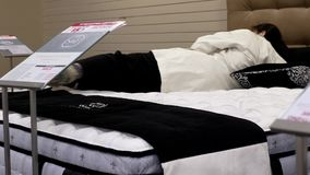 Woman trying new mattress. Inside Hudson's Bay store stock video