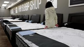 Woman trying new mattress. Inside Sears store stock video footage