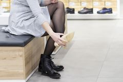 Woman trying on new shoes in shoe store. Buy new shoes in boutique of shopping center. view of feet of girl who wears shoes. Stock Photos