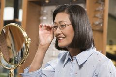 Woman Trying Out Glasses Stock Image