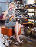 Woman trying on pair of sandals stock photo