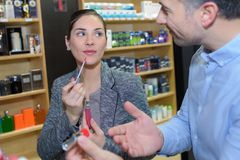 Woman trying product in beauty shop stock images