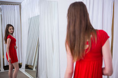 Woman trying on a red dress Stock Images