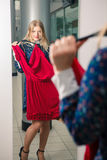 Woman trying red dress shopping for clothing Stock Image