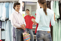Woman trying on red top in clothes shop, looking at reflection in mirror, boyfriend looking on, smiling, rear view.  stock image