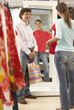 Woman trying on red top in clothes shop, looking at reflection in mirror, boyfriend looking on, smiling, rear view.  stock photo