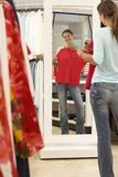 Woman trying on red top in clothes shop, looking at reflection in mirror, smiling, rear view royalty free stock photos