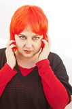 Woman trying on red wig. Young woman trying to decide if she likes herself while trying on a red wig on a bright white background Royalty Free Stock Images