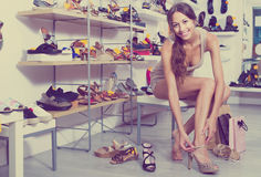 Woman trying on sandals in shoe store stock photo