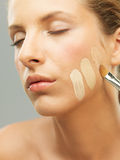 Woman trying shades of foundation on jaw. Closeup portrait woman trying different shades foundation Royalty Free Stock Photos