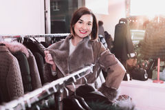 Woman trying on sheepskin coat in women's cloths store Stock Photography