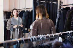 Woman trying on sheepskin coat in women's cloths store royalty free stock photo