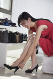 Woman trying on shoes at fashion store Stock Images