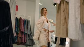 Woman trying on suit in boutique.
