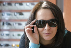 Woman trying on sunglasses Royalty Free Stock Photos