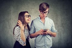 Woman trying to bring attention of a handsome man ignoring her using a smartphone. Attractive women trying to bring attention of young handsome men ignoring her Stock Images