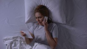 Woman trying to call to her man lying in bed and looking at photo, betrayal