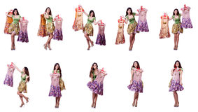 The woman trying to choose dress on white. Woman trying to choose dress on white Royalty Free Stock Images