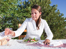 Woman trying to clean after spilling wine. Embarrassed young woman trying to clean after spilling wine on white table cloth Stock Photo