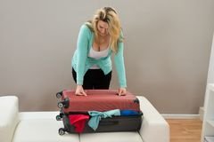 Woman trying to close the suitcase. Woman Trying To Close The Overfilled Suitcase In The Room Royalty Free Stock Photos