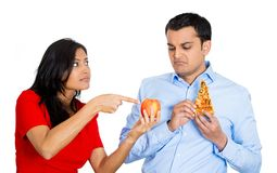 Woman trying to convince man to eat healthy food Stock Photography