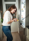 Woman trying to cut chain on fridge with pliers Royalty Free Stock Photography