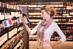 Woman trying to decide which bottle of wine to buy stock photography