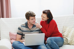 Woman trying to distract boyfriend from laptop Royalty Free Stock Image