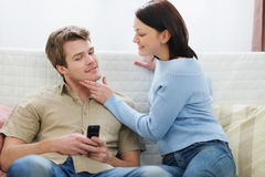 Woman trying to distract boyfriend from mobile Stock Image