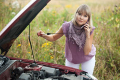 Woman trying to fix the car. Young woman trying to fix the car Stock Photo