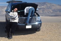 Woman trying to fix car while husband relaxes stock photography