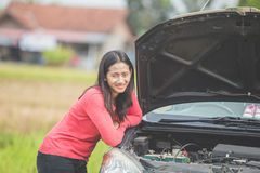 Woman trying to fix her broken car Royalty Free Stock Photography