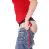 Woman trying to get in to old jeans. Royalty Free Stock Photos