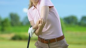 Woman trying to hit golf ball but feeling elbow pain rising club, joint problems stock video