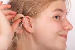 Woman trying to insert a hearing aid into ear Royalty Free Stock Photos