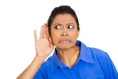 Woman trying to listen. Closeup portrait of nosy worried funny woman, hand to ear, trying to listen to juicy gossip conversation and mad angry upset from hearing Royalty Free Stock Image