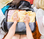 Woman Trying To Pack Clothes In A Bag Royalty Free Stock Photo