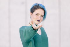 Woman trying to reach you pointing her hand to the front. Woman with blue hair and blue clothes trying to reach you pointing her hand to the front Royalty Free Stock Photo