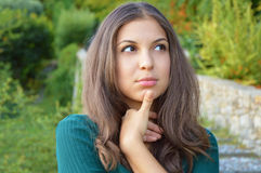 Woman trying to remember. Close up portrait headshot young lady girl with thumb on chin thinking daydreaming deeply about somethin. G looking up  outdoor Royalty Free Stock Photography
