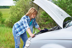 Woman trying to repair broken car Royalty Free Stock Image