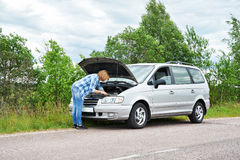 Woman trying to repair broken car Stock Photos