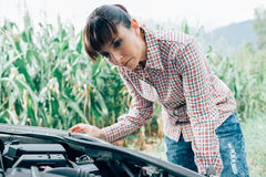 Woman trying to repair her broken car Stock Photos