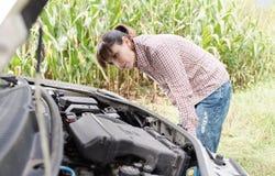 Woman trying to repair her broken car Stock Image